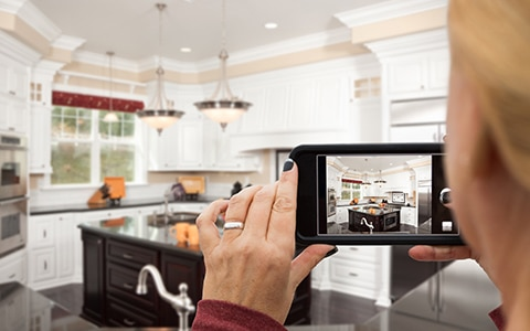 Woman using phone to take a video of a model home for sale