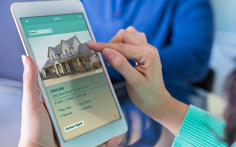 Woman searching home listings on a tablet