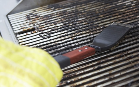 Person cleaning a gs grill