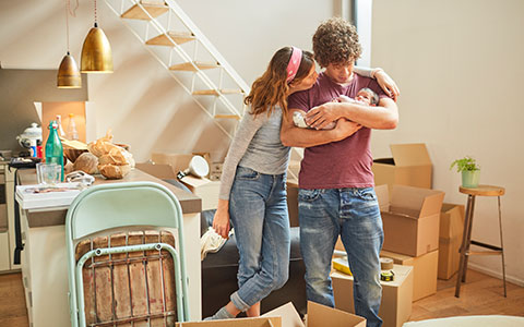 Couple inside home with moving boxes holding a baby-How Often Should I Review My Insurance Coverage?