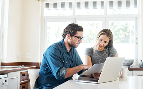 man and woman comparing home and mortgage insurance
