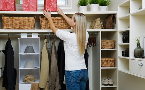 woman reaches up while organizing closet, 10 smart things to do while you're stuck at home
