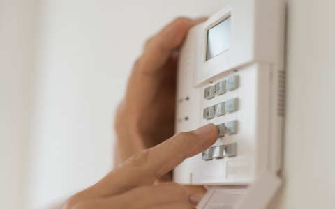 person typing on home alarm system