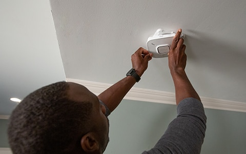 Human installing a smart home smoke dectector