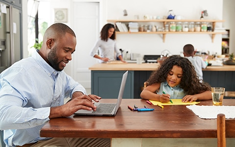 man working at table with daughter, 6 home organizing projects to keep your children busy while you're working from home