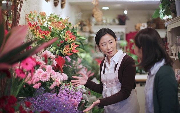 small business owner talking with customer in floral shop