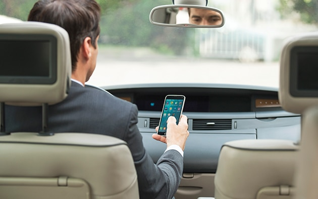 man looking at phone in car
