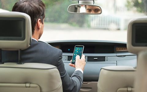 man looking at phone while driving