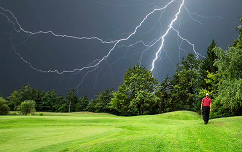 Golfer walking outside during lightning storm