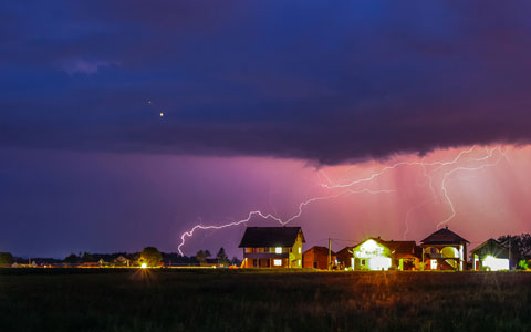 Lightning across sky above houses