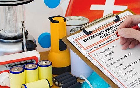 a hand checks off items on an emergency preparedness list, Preparing for Hurricanes During the COVID-19 Pandemic