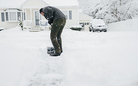 person shoveling their driveway after a winter storm
