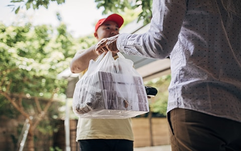 Food service delivery person delivering food to a homeowner