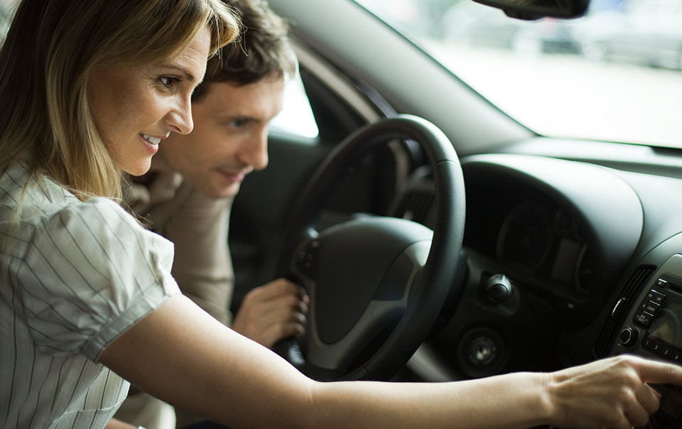 Couple sitting in new car and deciding if should buy a new car