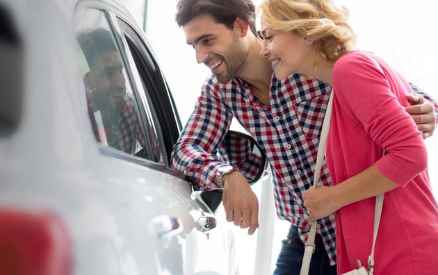 Younger couple looking at new cars at car dealership