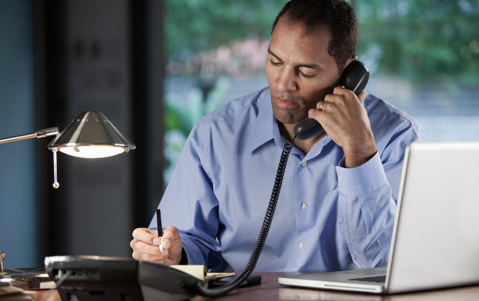 Man talking with agent on phone about how to lower car insurance costs