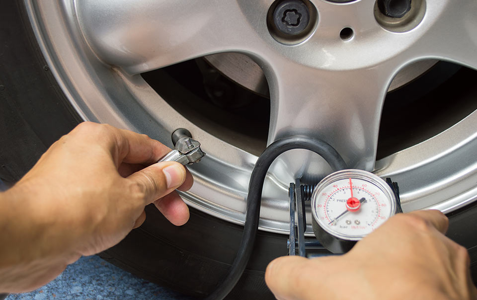 Person testing tire pressure as part of car maintenance checklist