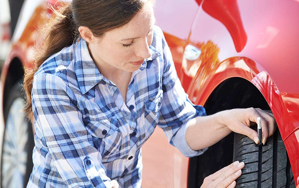 Woman checking tire tread of car as part of regular car maintenance routine