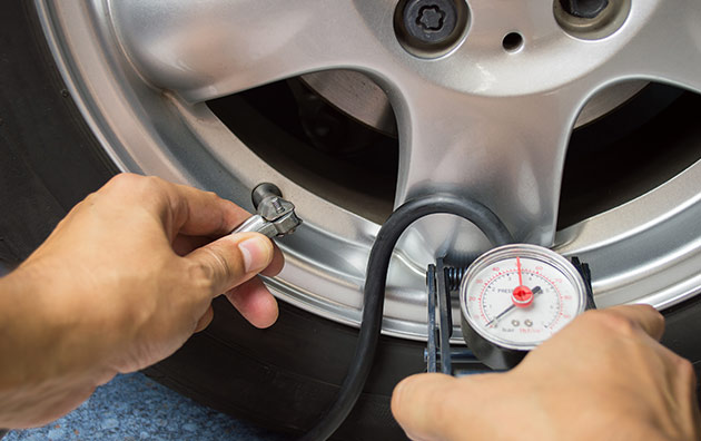 Person checking tire pressure as part of car maintenance