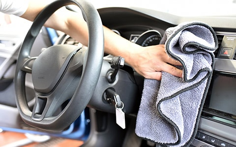 Person using rag to clean interior of car