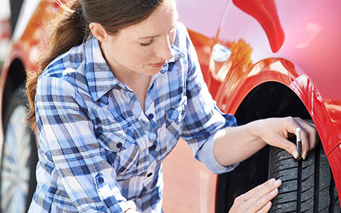 Woman checking tire tread as part of regular car maintenance routine