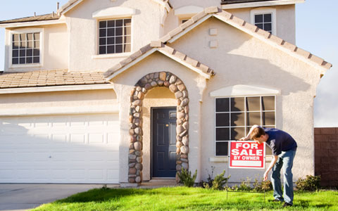 Person putting up For Sale by Owner sign in front of house