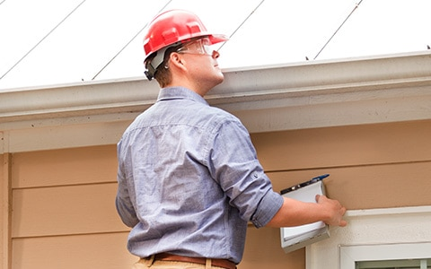 Home inspector looking at roof of house