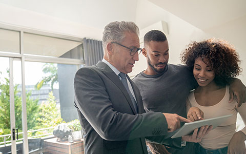 couple filling out home insurance papers with agent