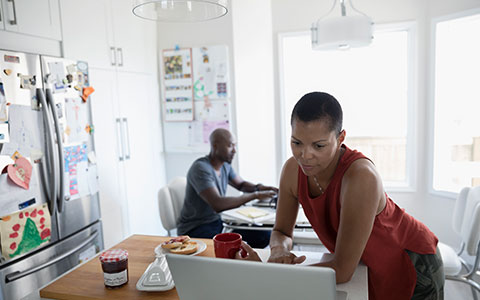 couple researching bundling insurance in kitchen