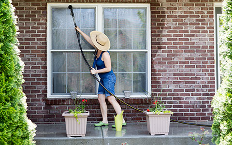 Woman cleaning outside of windows in summer