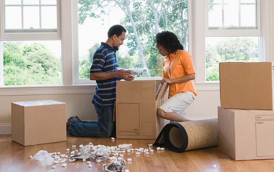 Couple in house packing to move