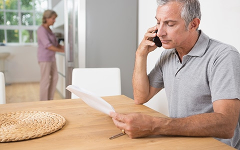 Man speaking on phone with agent about insurance claim process