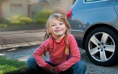 girl sitting in front of car
